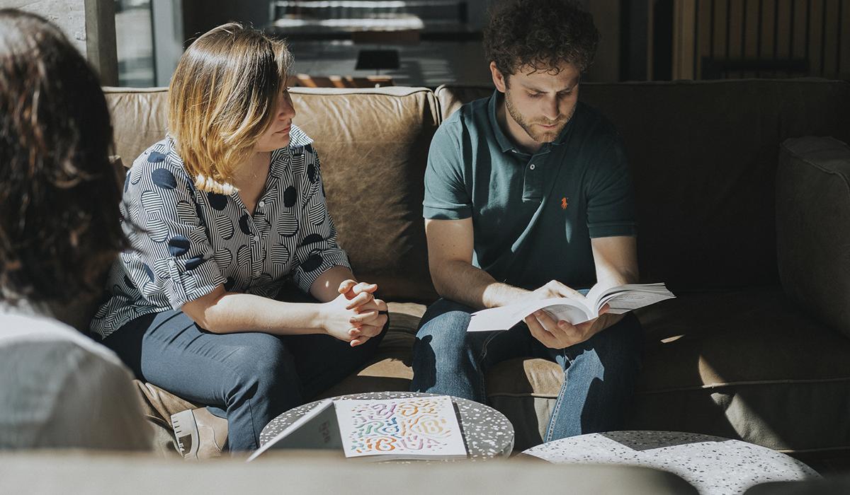 fotografía del equipo de EgaleCo Lab, dos mujeres y un hombre, hablando relajadamente en un sofá