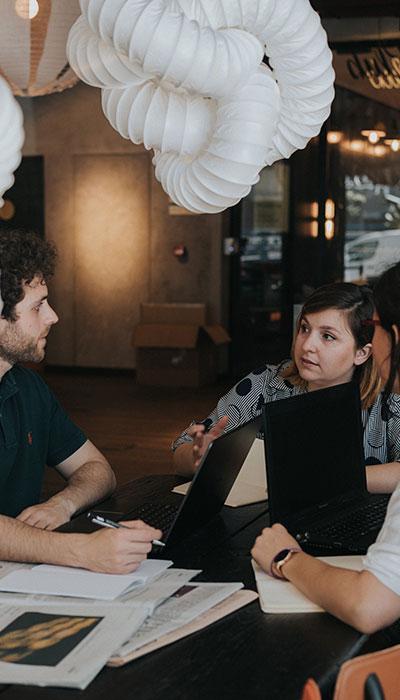 equipo de EgaleCo Lab hablando alrededor de una mesa con ordenadores