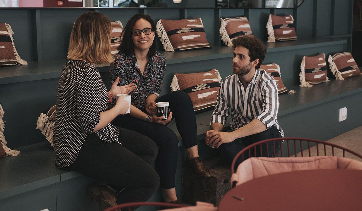 fotografía del equipo de EgaleCo Lab, dos mujeres y un hombre, hablando relajadamente con una taza del grupo musical de los Beatles