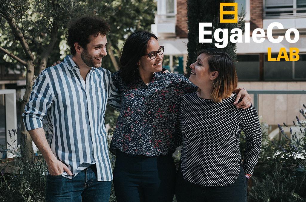 foto del equipo de consultores de género de EgaleCo Lab formado por dos mujeres y un hombre que se miran con complicidad, superpuesto el logo de EgaleCo Lab