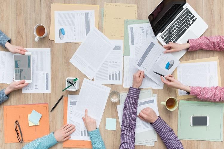 equipo de trabajo simulando trabajar en un plan de igualdad con material de oficina